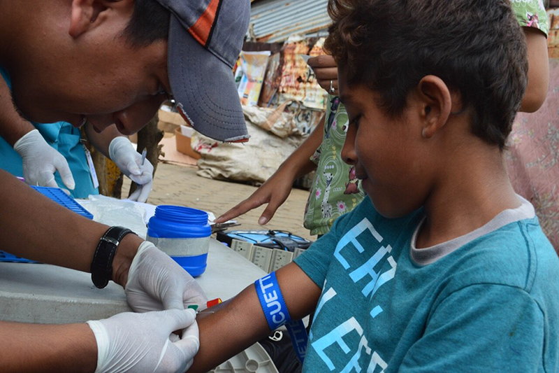 Researcher collects blood sample from a child