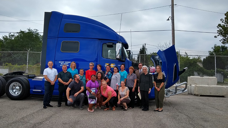SDEV workers with a low emission class-eight tractor-trailer truck