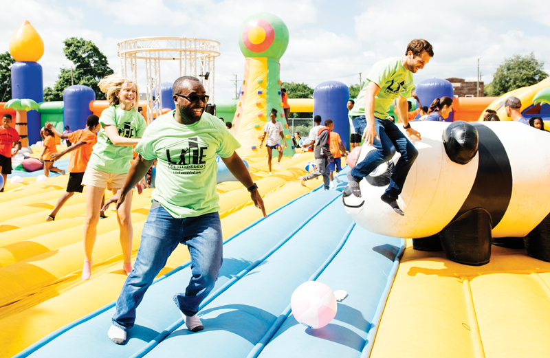 30 in Their Thirties honorees enjoy a bounce house at Life Remodeled's Family Fun Day