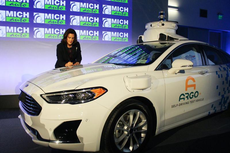 Gov. Gretchen Whitmer signing documents on car