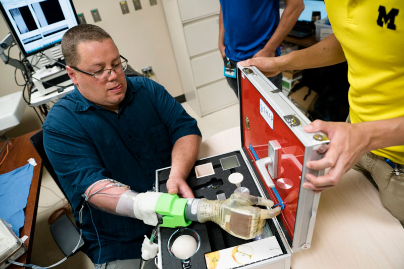 Joe Hamilton using U-M robotic prosthetic hand